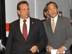 Nassau County Executive Edward Mangano and Islanders owner Charles Wang enter a news conference Monday night.
