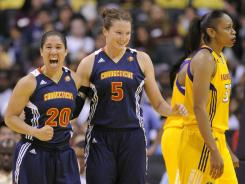 The Sun's Kara Lawson, left, celebrates a basket with teammate Kelsey Griffin, center, as the Sparks' Tina Thompson looks on during Connecticut's 79-70 win Wednesday in Los Angeles.