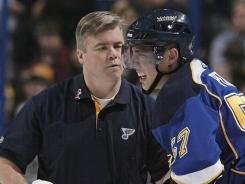 David Perron is helped off the ice by trainer Ray Barile after taking a hit from Sharks center Joe Thornton on Nov. 4.