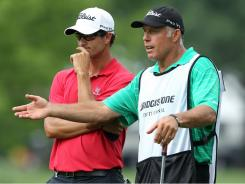 Adam Scott of Australia talks with caddie Steve Williams after making birdie on the 17th hole during the first round of the WGC-Bridgestone Invitational.