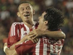 Chivas' Giovanny Casillas, left, and Jose Luis Verduzco celebrate after Verduzco scores the fourth goal in a 4-1 win over Barcelona.