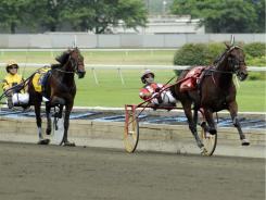 George Brenna and Broad Bahn, right, pulls away from Whiskey Tax (6) on the way to winning the Hambletonian harness horse race.
