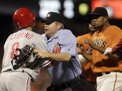 Shane Victorino, left, is restrained by home plate umpire Mike Muchlinski, after the Phillies' outfielder was hit by a pitch by Giants reliever Ramon Ramirez, right, during the sixth inning.