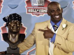 Deion Sanders poses with a bust of himself during the induction ceremony at the Pro Football Hall of Fame, Saturday in Canton, Ohio.