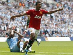Manchester United's Nani (right) celebrates after scoring the winning goal against Manchester City during their English FA Community Shield soccer match at Wembley Stadium in London on Sunday.