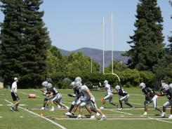 The Oakland Raiders go through a warmup drill during training camp in Napa, Calif., on Aug. 4.