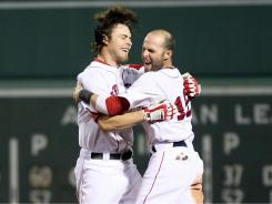Josh Reddick, left, is congratulated by teamamte Dustin Pedroia hitting an RBI single to win the game in the 10th inning.