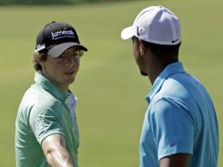 Rory McIlroy shakes hands with Tiger Woods on the range at the PGA Championship on Wednesday.