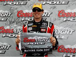 Kyle Busch poses in victory lane after qualifying for the pole position in the Heluva Good! Sour Cream Dips at the Glen.
