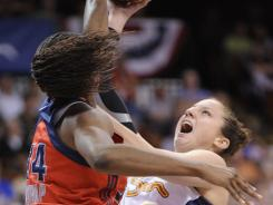 The Sun's Kelsey Griffin, right, shoots over the Mystics' Victoria Dunlap on Saturday. Connecticut held Washington scoreless for five minutes in the fourth quarter en route to the 82-75 victory.