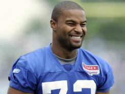 Osi Umenyiora, seen here watching practice in East Rutherford, N.J. on Aug. 4, will actually return to practice despite not getting the new contract he wanted.