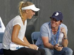 Rory McIlroy, right, chats it up with Caroline Wozniacki on Sunday during her tennis practice session at the Western and Southern Open in Mason, Ohio.
