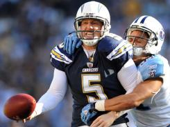 Chargers holder Mike Scifres, left, is clutched by the Titans' Michael Griffin on Oct. 31, 2010 after fumbling the snap duringapoint-after try.