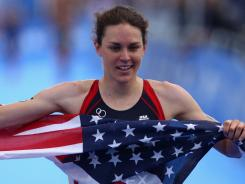 In a file photo from Aug. 6, Gwen Jorgensen of the USA celebrates as she crosses the line to take silver in the Dextro Energy Triathlon ITU World Championship Series in Hyde Park in London.