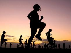 Members of the Hays High School football team begin their first practice of the season before sunrise in Hays, Kan., on Monday. The team works out at 6:30 a.m. and 6:30 p.m. for the first week to get acclimated to the heat.