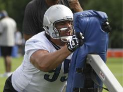 Detroit Lions defensive tackle Quinn Pitcock hits a tackling sled during drills. He hopes to make a comeback with the team.