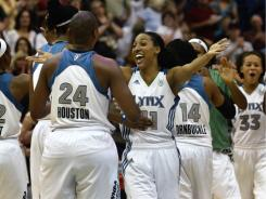 Candice Wiggins (11) celebrates with teammate Charde Houston (24) and the rest of the Minnesota Lynx after beating the Los Angeles Sparks 87-68 Saturday night in Minneapolis.