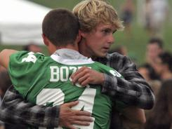 A mourner wearing the #34 Mainland Football jersey of Edgar Bozzi hugs a Mainland Regional High School student during a memorial vigil for four members of the school's football team, including Bozzi.
