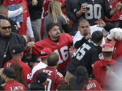 "Football fans fight in the stands during  the exhibition game between the 49ers and Raiders in San Francisco. After two men were shot and wounded following the game, the NFL and the mayors of the two cities jointly called for an end to ""intimidation"" and acts of violence at sporting events."