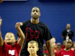 Hate for Heat cooling? Dwyane Wade, working with kids at abasketball camp last month, says disdain for the Heat is dropping.
