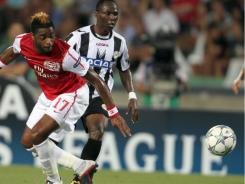 Arsenal's midfielder Alex Song of Cameroon (left) and Udinese's midfielder Emmanuel Agyemang of Ghana challenge for the ball during their Champions League qualifying playoff second leg soccer match in Udine, Italy, on Wednesday.