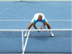 The I formation: Xavier Malisse of Belgium crouches down at the net, while partner Mark Knowles of the Bahamas serves over him.