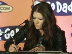 Danica Patrick signs a contract to drive full time in the NASCAR Nationwide Series circuit and select Sprint Cup races during a news conference Thursday.