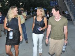 Golfer Rory McIlroy, right, walks with tennis star Caroline Wozniacki, left, and tennis tournament director Anne Worcester on Thursday at the New Haven Open.