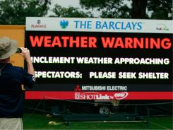A spectator takes a picture of a sign annoucing the gathering storm on Thursday at The Barclays.