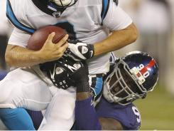 Giants defensive end Jason Pierre-Paul, right, brings down Panthers quarterback Jimmy Clausen for a sack during their Aug. 13 preseason game.