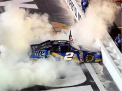 Brad Keselowski smokes his tires while carrying out his tradition of holding an American flag to the fans after wins.