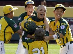 Nick Pratto, center, and his Huntington Beach teammates celebrate their Little League World Series title.
