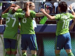 Lamar Neagle (27) celebrates with teammates Erik Friberg (8) and Mauro Rosales (10) during the Seattle Sounders 6-2 rout of the Columbus Crew on Saturday.