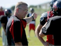 Dwight Richins, head football coach at Shelley High School in Idaho, goes over a play during practice on Wednesday. Ritchins left his coaching duties behind in 2010 to serve a tour of duty in Afghanistan.