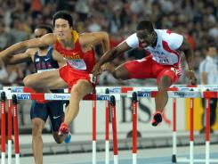 Liu Xiang (left) and Dayron Robles compete in the 110 hurdles in the IAAF World Championships in  Daegu, South Korea on Monday.