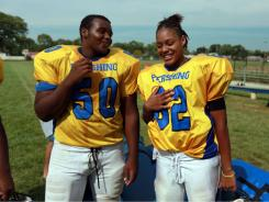 Antonious Turner, 14, ,left, and Monique Howard, 16, share a laugh during  football practice at Detroit Pershing on Tuesday, Howard plays right tackle on Pershing's offensive line.