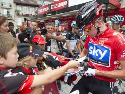 Overall leader Bradley Wiggins of Britain signs autographs in Ponteareas, Spain, before the start of the 12th stage of the Spanish Vuelta on Thursday. Wiggins kept the overall lead.