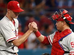 Ryan Madson, left, and Carlos Ruiz celebrate following the Phillies' win Friday over the Marlins. The win sends Philadelphia 42 games above .500 for the first time in the franchise's 129-year history.