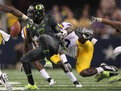 Oregon's De'Anthony Thomas fumbles after a hit by LSU on a kickoff return in the third quarter.