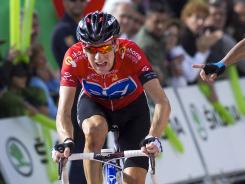 Bradley Wiggins crosses the finish line of the 14th stage of the Spanish Vuelta . He extended his overall lead as Rein Taaramae  won the stage.