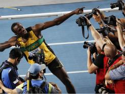 Jamaica's Usain Bolt (center) poses for photographers as he celebrates winning the men's 200 final at the World Athletics Championships in Daegu, South Korea, on Saturday.