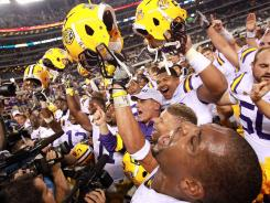 LSU coach Les Miles celebrates with his team after defeating the Oregon Ducks at Cowboys Stadium.