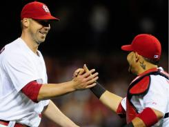 Cardinals starter Chris Carpenter, left, receives congratulations from catcher Yadier Molina after throwing a shutout against the Brewers at Busch Stadium in St. Louis.