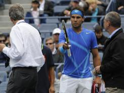 Rafael Nadal registers his complaints to tournament officials because of the wet courts.