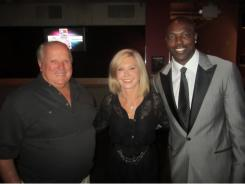 A.J. Foyt, left, singer Olivia Newton-John and NFL star Terrell Owens pose at the Pink & Blue For Two charity event Sept. 3 in Baltimore.