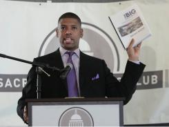 "Sacramento Mayor Kevin Johnson displays a copy of the various proposals put together by ""Think Big Sacramento"" to raise nearly $400 million to build a new downtown arena in the city."