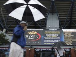 Fans walk near Arthur Ashe Stadium during one of many rain delays Wednesday at the U.S. Open.