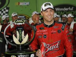 Kevin Harvick stands with the winner's trophy after winning the Wonderful Pistachios 400 Saturday at Richmond International Raceway.