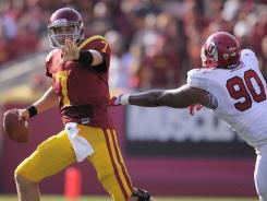 Southern California quarterback Matt Barkley  gets set to pass under pressure from Utah defensive end Derrick Shelby.