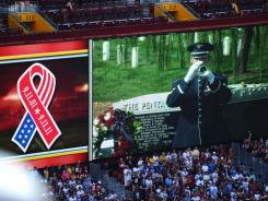The video screen at FedEx Field displays Taps being played at Arlington National Cemetary during a 9/11 tribute.